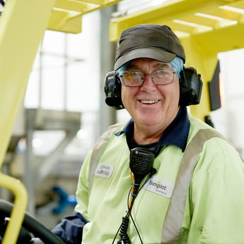 Picture of J.R. Simplot Company Australian employee in safety gear driving forklift in warehouse.
