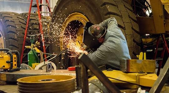 Picture of transportation maintenace worker welding heavy equipment in shop.