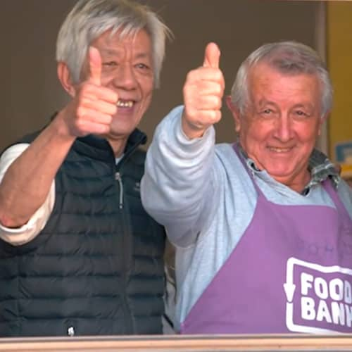 Picture of two adult volunteers giving the thumbs up sign at a community breakfast event.